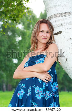 Smiling beautiful woman leaned against a birch tree. Summertime