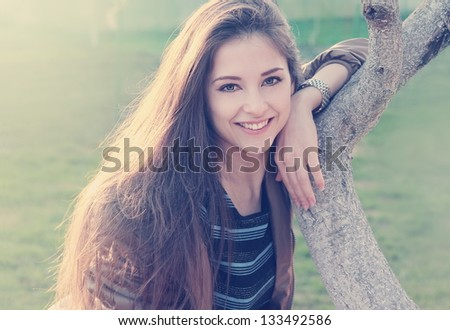 Smiling beautiful woman near tree outdoors summer background looking happy - stock photo