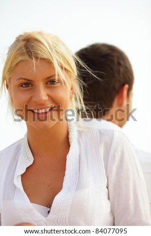 Smiling beautiful woman outdoor, man on the background - stock photo