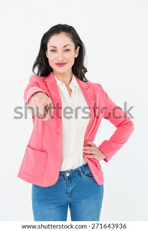 Smiling beautiful woman pointing with her finger on white background