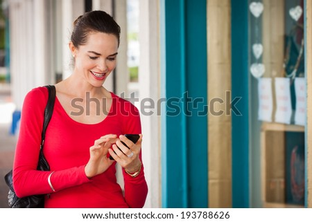 Smiling beautiful woman texting on a mobile or smart phone whilst out shopping. - stock photo