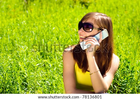 Smiling beautiful woman with mobile phone outdoor. Sunny summer day. - stock photo