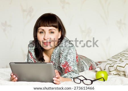 Smiling beautiful woman with tablet on her bed - stock photo