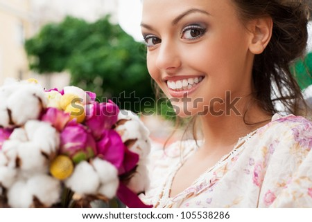 smiling beautiful young girl with bouquet of flowers. Outdoors - stock photo
