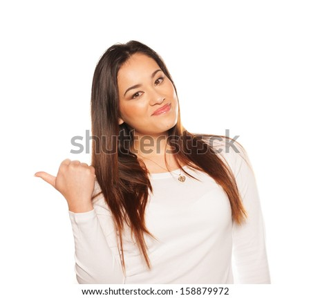 Smiling beautiful young woman gesturing with her thumb either giving a thumbs up gesture of approval and success or thumbing a lift isolated on white