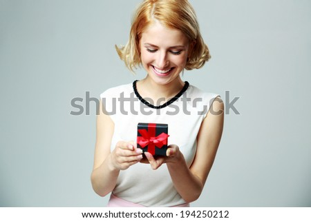 Smiling beautiful young woman holding an open jewelery gift box - stock photo