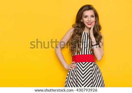 Smiling beautiful young woman in black and white striped dress posing with hand on chin and looking away. Three quarter length studio shot on yellow background. - stock photo