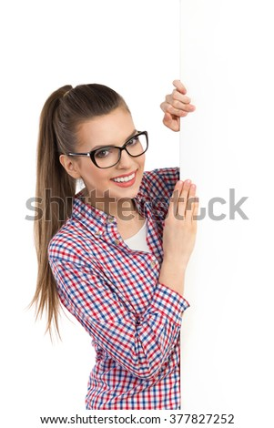Smiling beautiful young woman in glasses and lumberjack shirt standing behind white banner and holding it. Waist up studio shot isolated on white. - stock photo