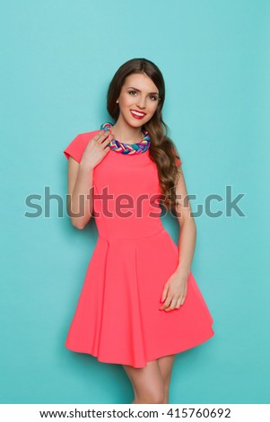 Smiling beautiful young woman in pink mini dress posing with hand on shoulder and holding colorful braided necklace. Three quarter length studio shot on turquoise background. - stock photo