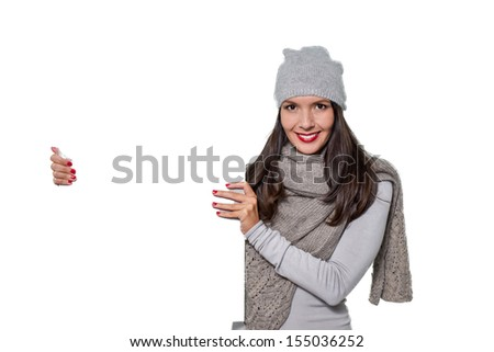Smiling beautiful young woman in stylish winter fashion holding a blank white sign with copyspace for your text or advertisement