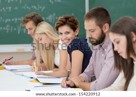Smiling beautiful young woman in the classroom sitting in a line of students working together at a long table, turning to smile at the camera - stock photo