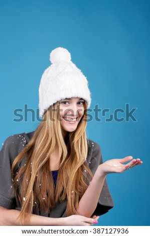 Smiling beautiful young woman in white winter hat over blue background - stock photo