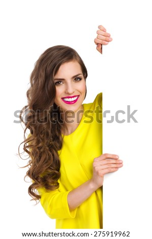 Smiling beautiful young woman in yellow top standing behind vertical big white placard and holding it. Waist up studio shot isolated on white. - stock photo