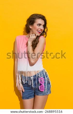Smiling beautiful young woman looking away. Three quarter length studio shot on yellow background. - stock photo