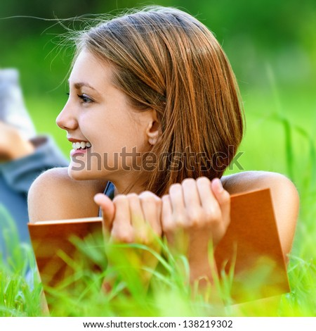 Smiling beautiful young woman lying on grass and reading book, against background of summer green park. - stock photo