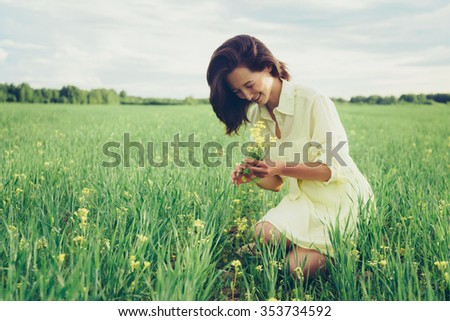 Smiling beautiful young woman picking yellow wildflowers on meadow in summer