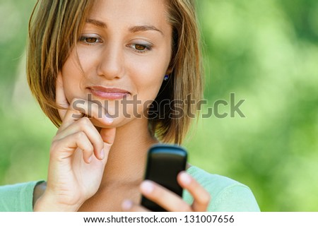 Smiling beautiful young woman reads sms on mobile phone, against background of summer green park. - stock photo
