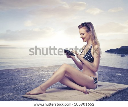 Smiling beautiful young woman sitting on a bath towel at the seaside and using a tablet pc - stock photo