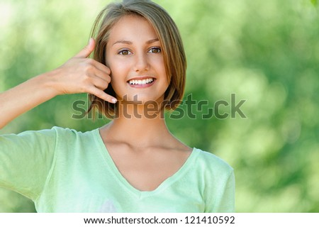 Smiling beautiful young woman talking on phone simulates, against background of summer green park. - stock photo