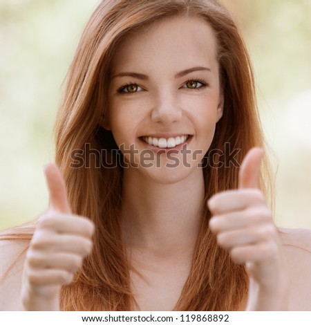 Smiling beautiful young woman with bare shoulders lifts thumbs upwards, against green of summer park. - stock photo