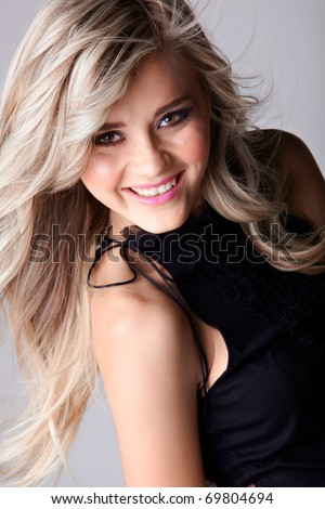 smiling beautiful young woman with long blond hair blowing in the wind with naturally beautiful skin - stock photo