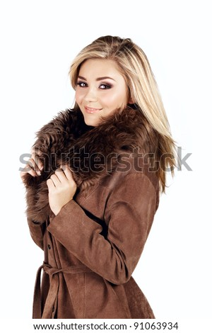 smiling beautiful young woman with long blond hair wearing a suede fur coat on studio background - stock photo