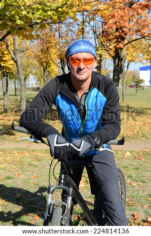Smiling bicyclist in autumn park - stock photo