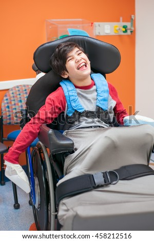 Smiling  biracial disabled little boy sitting in wheelchair at doctor's office.  - stock photo