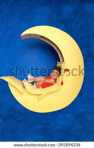 Smiling black baby girl on the moon against blue background. Dreams, child, happiness and people concept - stock photo