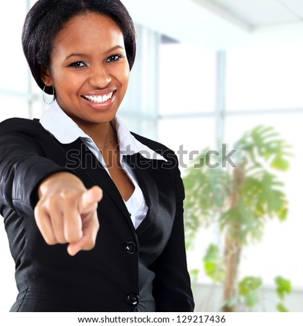 Smiling black business woman pointing on camera in office - stock photo