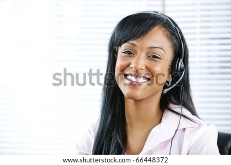 Smiling black customer service and support woman wearing headset - stock photo