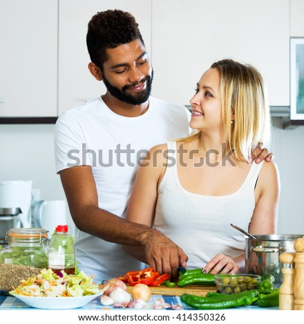 Smiling black husband helping white wife preparing healthy dinner - stock photo