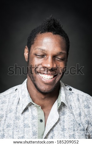 Smiling black man close up portrait against dark background.  - stock photo
