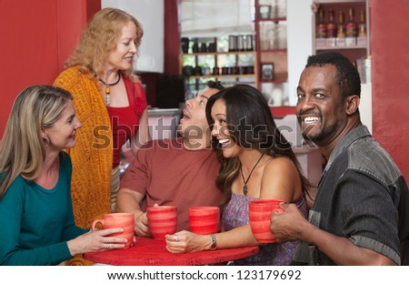 Smiling Black man drinking coffee with group of friends - stock photo