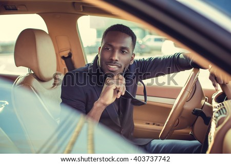 Smiling black man in a car. - stock photo