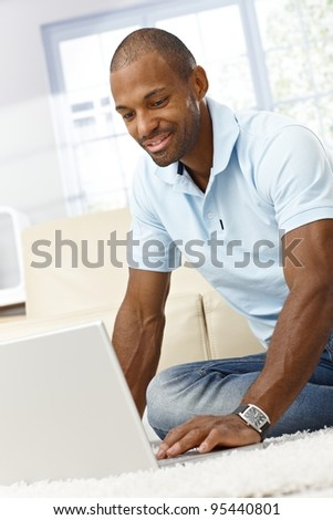 Smiling black man using laptop computer at home, sitting on floor.? - stock photo