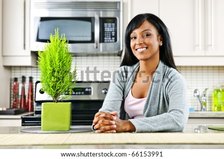 Smiling black woman in modern kitchen interior