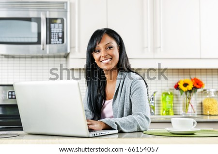 Smiling black woman using computer in modern kitchen interior - stock photo