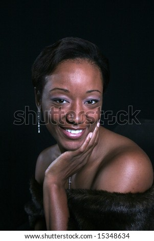 smiling black woman with hand on her chin - stock photo
