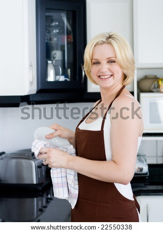 Smiling blond beautiful woman in the apron drying the dishes in the kitchen - stock photo