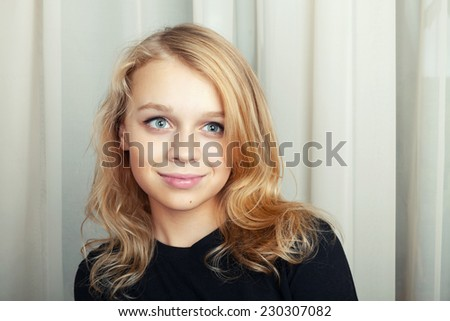 Smiling blond Caucasian girl closeup studio portrait - stock photo