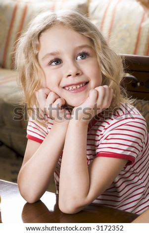 Smiling blond girl in stripe t-shirt sitting at the coffee table - stock photo