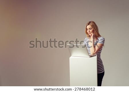 Smiling Blond Girl in Trendy Outfit Using her Laptop Computer on a High Stand Against Brown Background with Copy Space. - stock photo