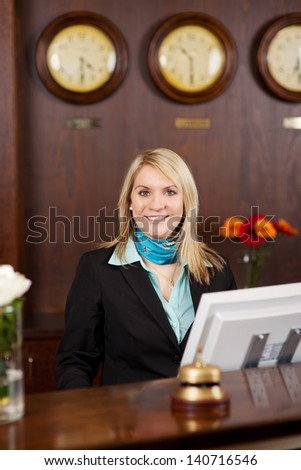 smiling blond receptionist behind the counter in hotel - stock photo