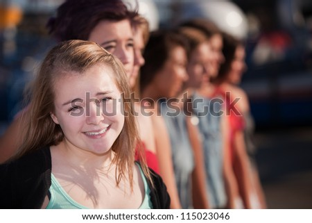 Smiling blond teenage girl in front of group - stock photo