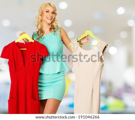 Smiling blond woman choosing clothes in a shopping mall  - stock photo