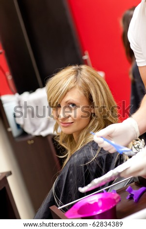 Smiling blond woman drying her hair in a hairdressing salon - stock photo