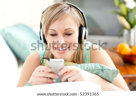 Smiling blond woman listening music lying on a sofa in the living-room - stock photo