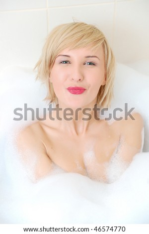 Smiling blond woman lying in bubble bath .