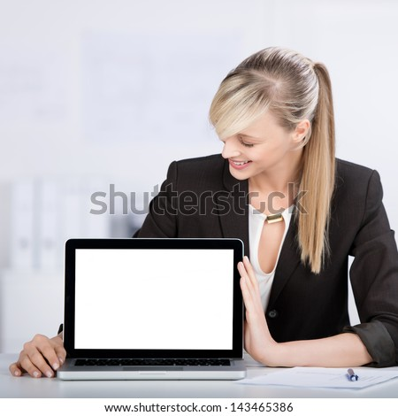 Smiling blond woman shows the laptop in a front view shot